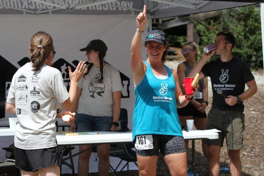 Mindy Smith, who worked with a group of local runners to prepare them for the Gateway 5K in Old Fort, celebrates her finish as the top female and second overall finisher in the race.