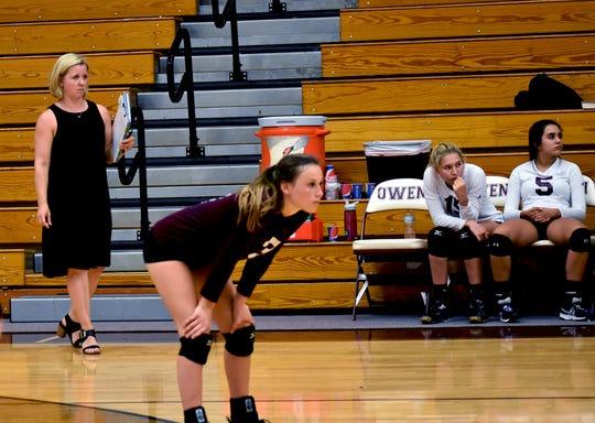 Second-year head coach Kim Clark surveys the court at Owen as senior Kathryn Wilkos prepares to return a serve.