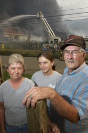 Vickie Wacaser, left, Amanda McLaughlin, and Freddie Wacaser stand in front of the Beacon Manufacturing building when it burned in 2003. Four generations of Vickie's family, including her grandfather, worked at the plant before it closed in 2002.