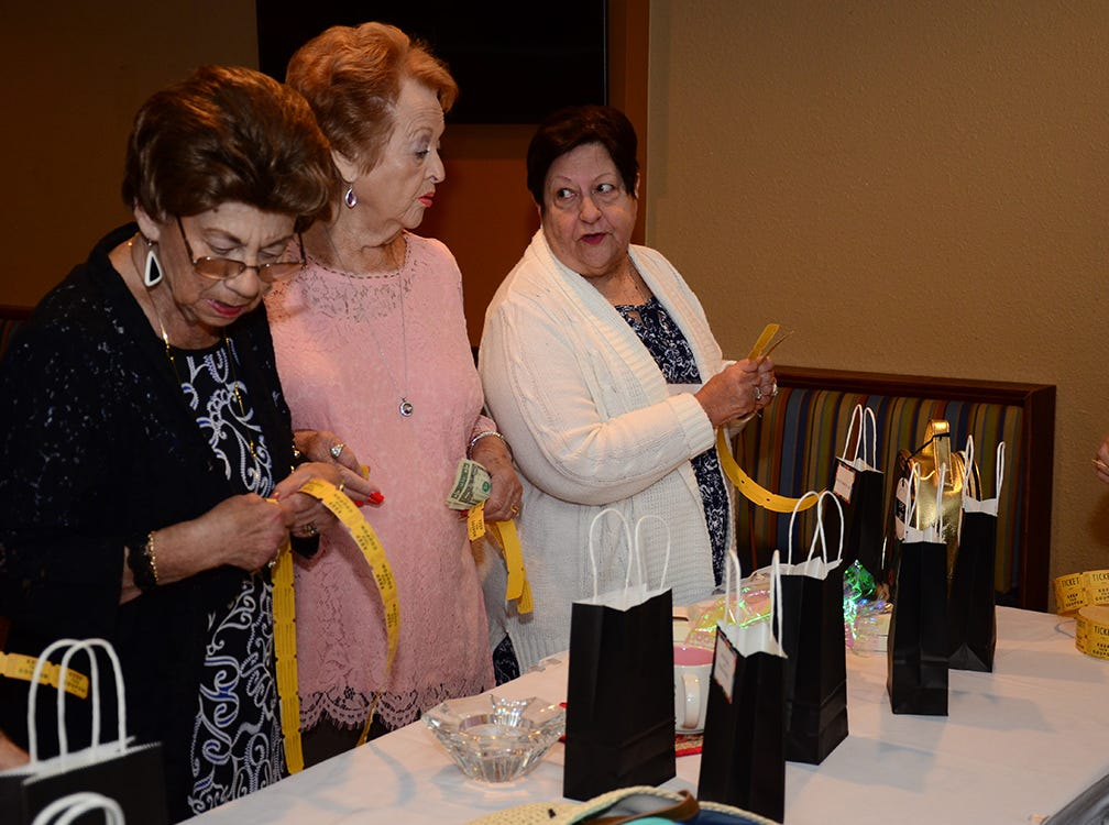 Joyce Hagan, Dot Murphy, and Cay Carrubba talk about the items up for auction Saturday during the A Quilt of Friendship luncheon held at The Tides Restaurant at Patrick Air Force Base.