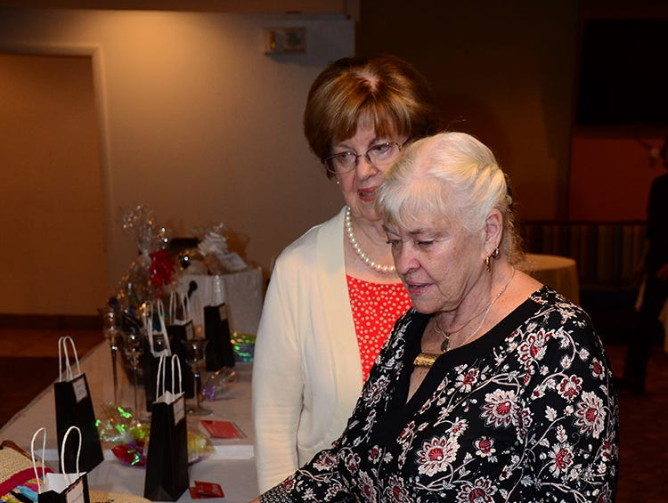 Pat Pascazi and Anne Duvall scan over the items up for auction during Beta Sigma Phi's luncheon held Saturday at Patrick Air Force Base.