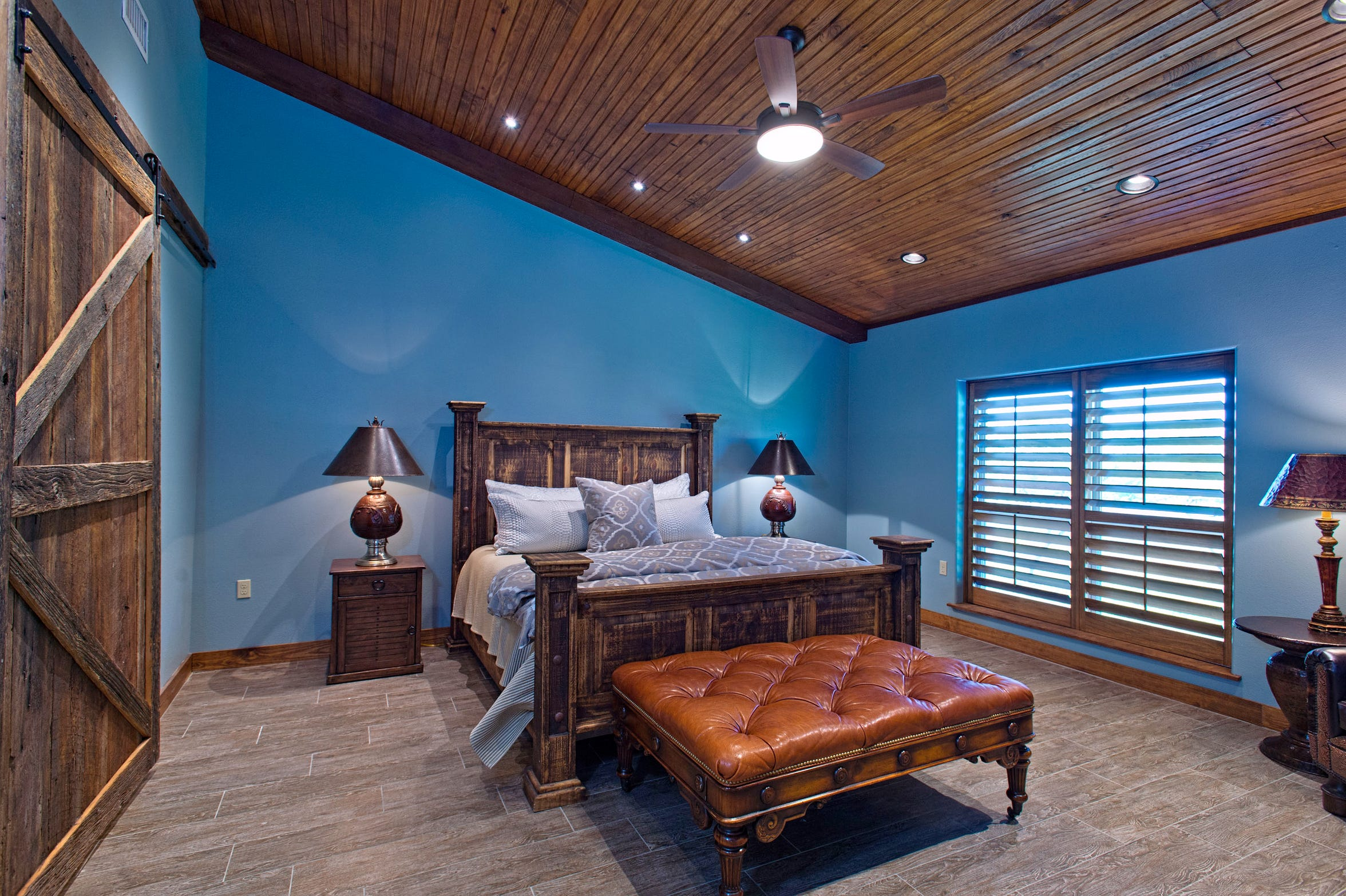 The oversized master bedroom is a restful spot with a vaulted wood ceiling, beautiful blue walls, plantain shuttered windows  and wood look tile flooring.