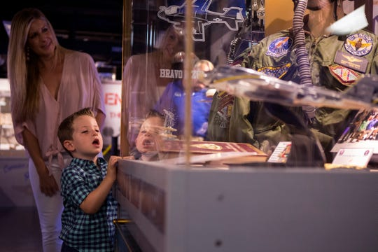 """The family of  Capt. Frank """"Rocco"""" Montesano, daughter Cariann Galloway (back) and grandson Case Galloway, 2, check out a display case dedicated to Frank """"Rocco"""" Montesano during the grand opening of the USS Lexington Museum on the Bay's new Carrier Row exhibit, which was dedicated to Montesano on Friday, Sept. 7, 2018. He was the executive director of the Lexington for 20 years. He died in April at age 68."""