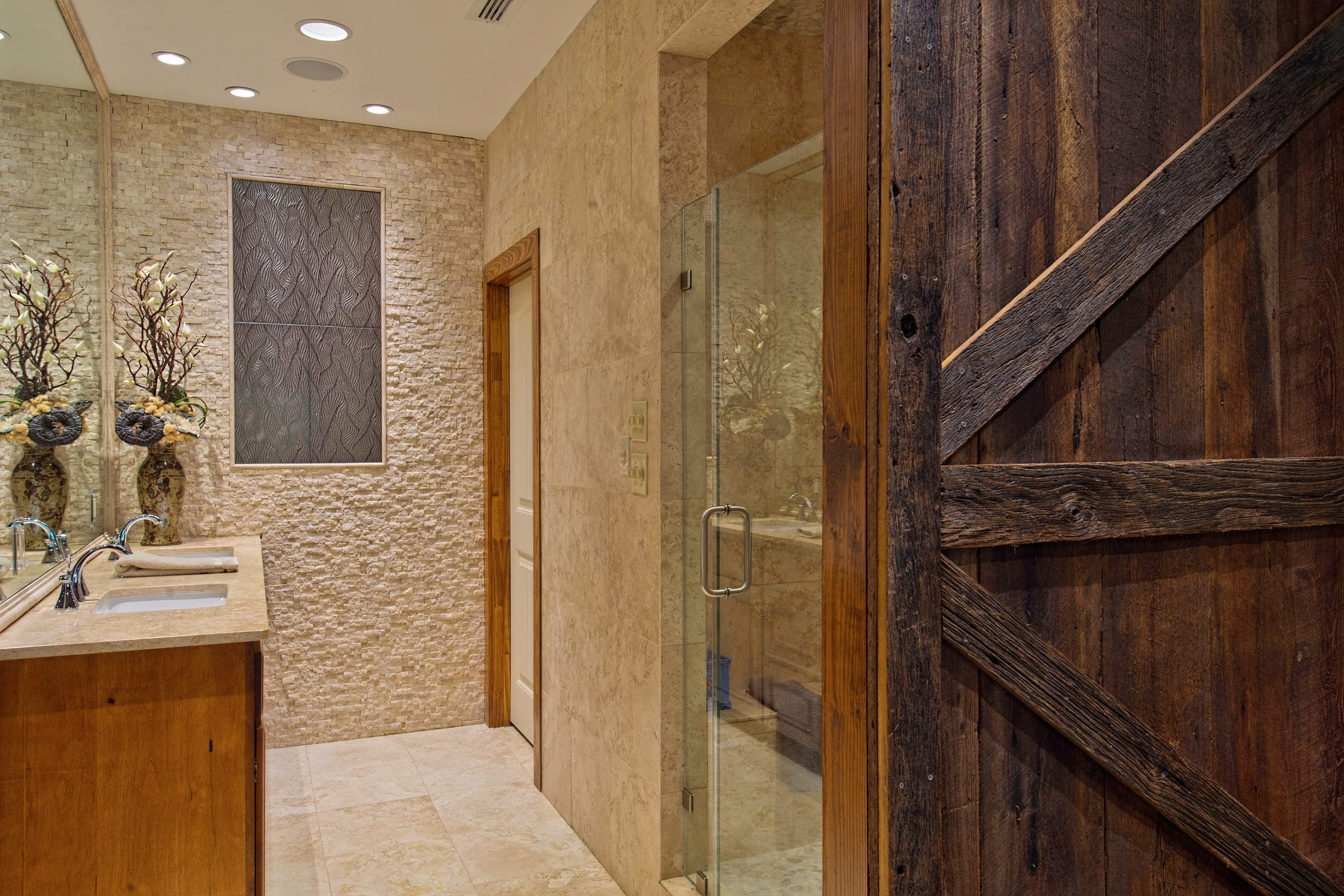 The beautiful master bath is a mix of granite, stone and tile with a frameless glass shower and a rolling barn door.