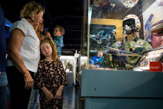 """The family of  Capt. Frank """"Rocco"""" Montesano, wife Joanne Montesano (clockwise from left), grandson Case Galloway, 2, and Kyleigh Galloway, 7, check out a display case dedicated to Frank """"Rocco"""" Montesano during the grand opening of the USS Lexington Museum on the Bay's new Carrier Row exhibit, which was dedicated to Montesano on Friday, Sept. 7, 2018. He was the executive director of the Lexington for 20 years. He died in April at age 68."""