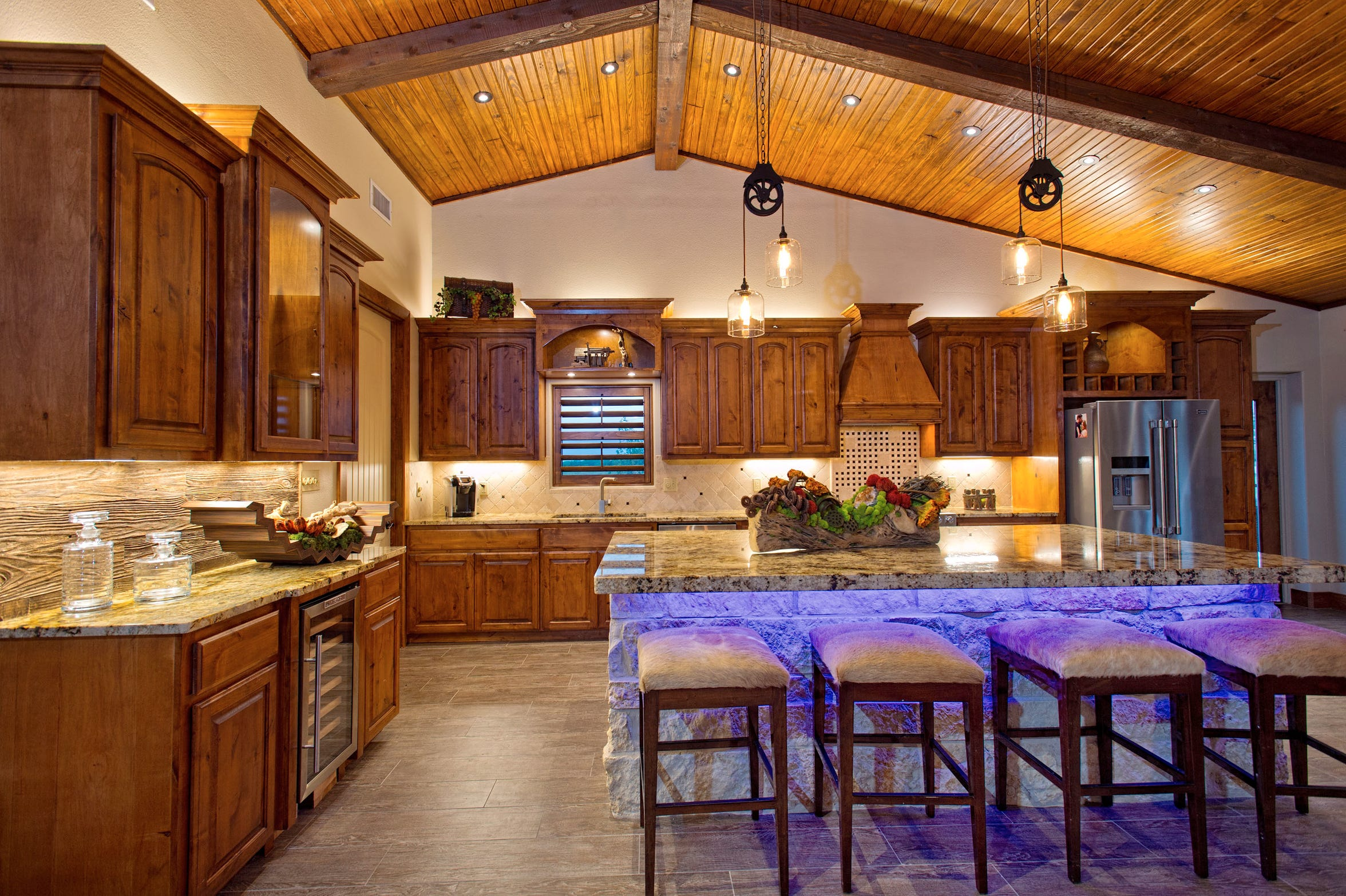 The stunning kitchen features a giant double stacked granite island with a stone base, wood beamed vaulted ceiling, granite counters, gorgeous custom knotty alder cabinets and dramatic lighting.