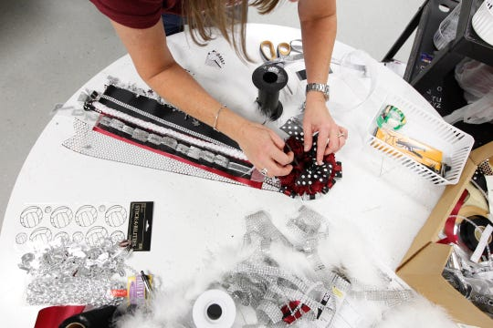 Lori Blades assembles a homecoming mum at Flour Bluff High School on Friday, October 17, 2014.