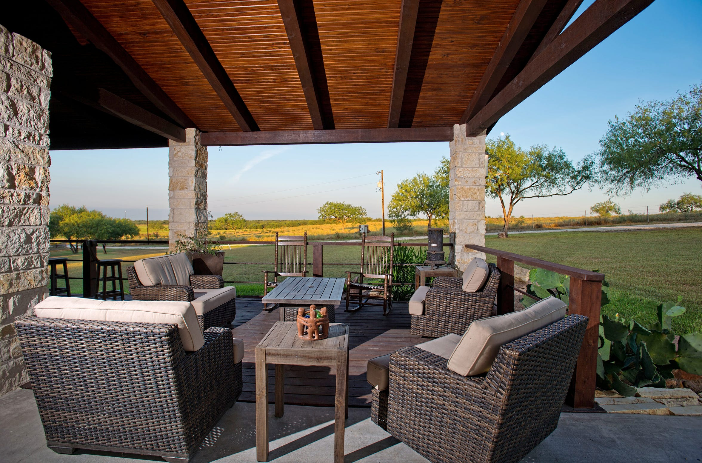 A peaceful spot to relax and enjoy the outdoors on the warp around porch overlooking the 3.33 acre mesquite tree covered lot.