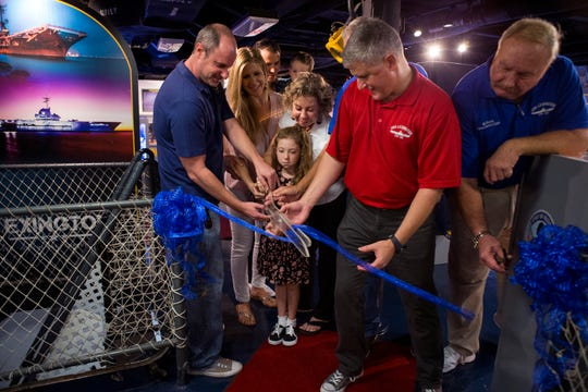 Steve Banta (center), executive director for the USS Lexington Museum on the Bay, cuts the ribbon during the grand opening of the museum's new Carrier Row exhibit, which was dedicated to Montesano on Friday, Sept. 7, 2018. He was the executive director of the Lexington for 20 years. He died in April at age 68.