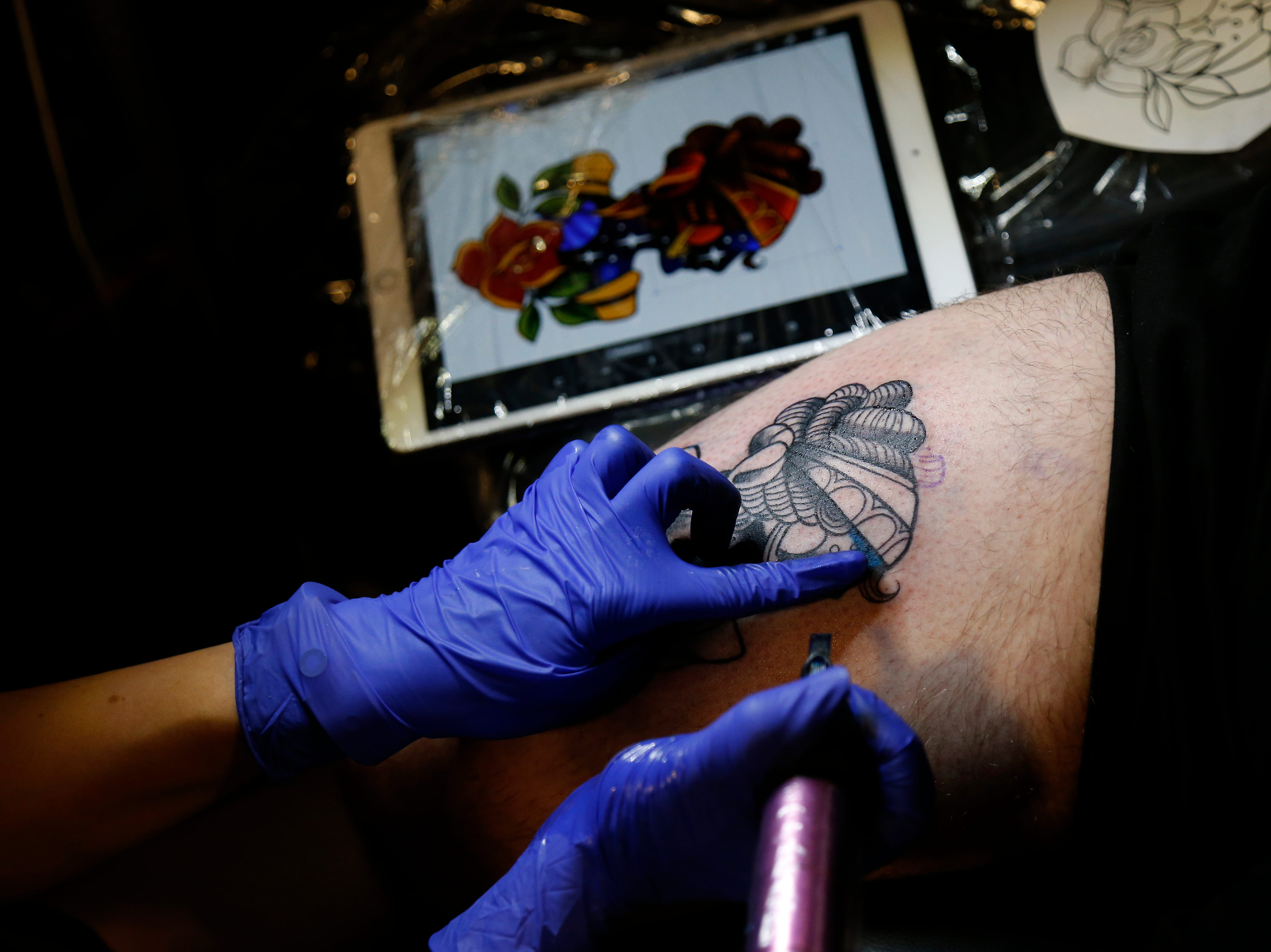 Amy Porter of Thin Line Tattoo in Batavia begins the color portion of a tattoo on Logan Pasqual, of Dayton, Ky., during the Greater Cincinnati Tattoo Arts Convention at the Northern Kentucky Convention Center in Covington, Ky., on Friday, Sept. 7, 2018.