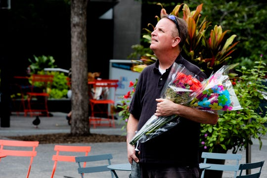 Larry Newcomer, brother of Richard Newcomer, 64, brings flowers before a vigil on Fountain Square in Downtown Cincinnati on Friday, Sept. 7, 2018. Richard Newcomer was fatally shot by Omar Santa Perez on Thursday during a mass shooting that left four dead including the shooter.