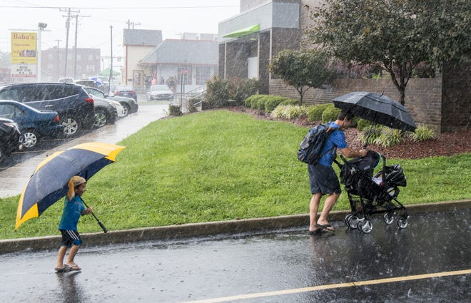 A family runs for cover during a thunderstorm before the start of the annual Harvest Home Parade Thursday, Sept. 6, 2018, in Cheviot.