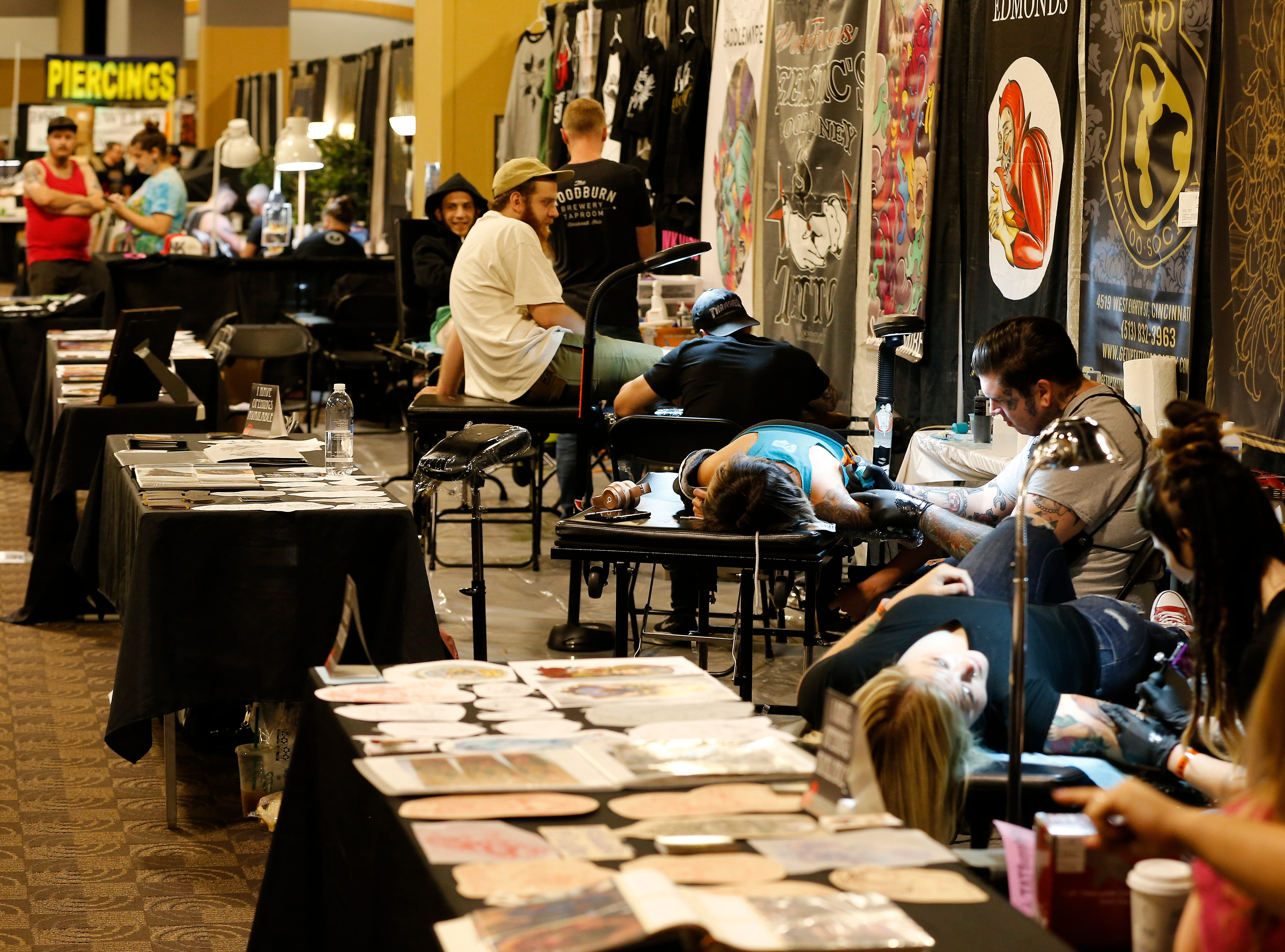 Visitors line up to receive new tattoos from visiting artists during the Greater Cincinnati Tattoo Arts Convention at the Northern Kentucky Convention Center in Covington, Ky., on Friday, Sept. 7, 2018.