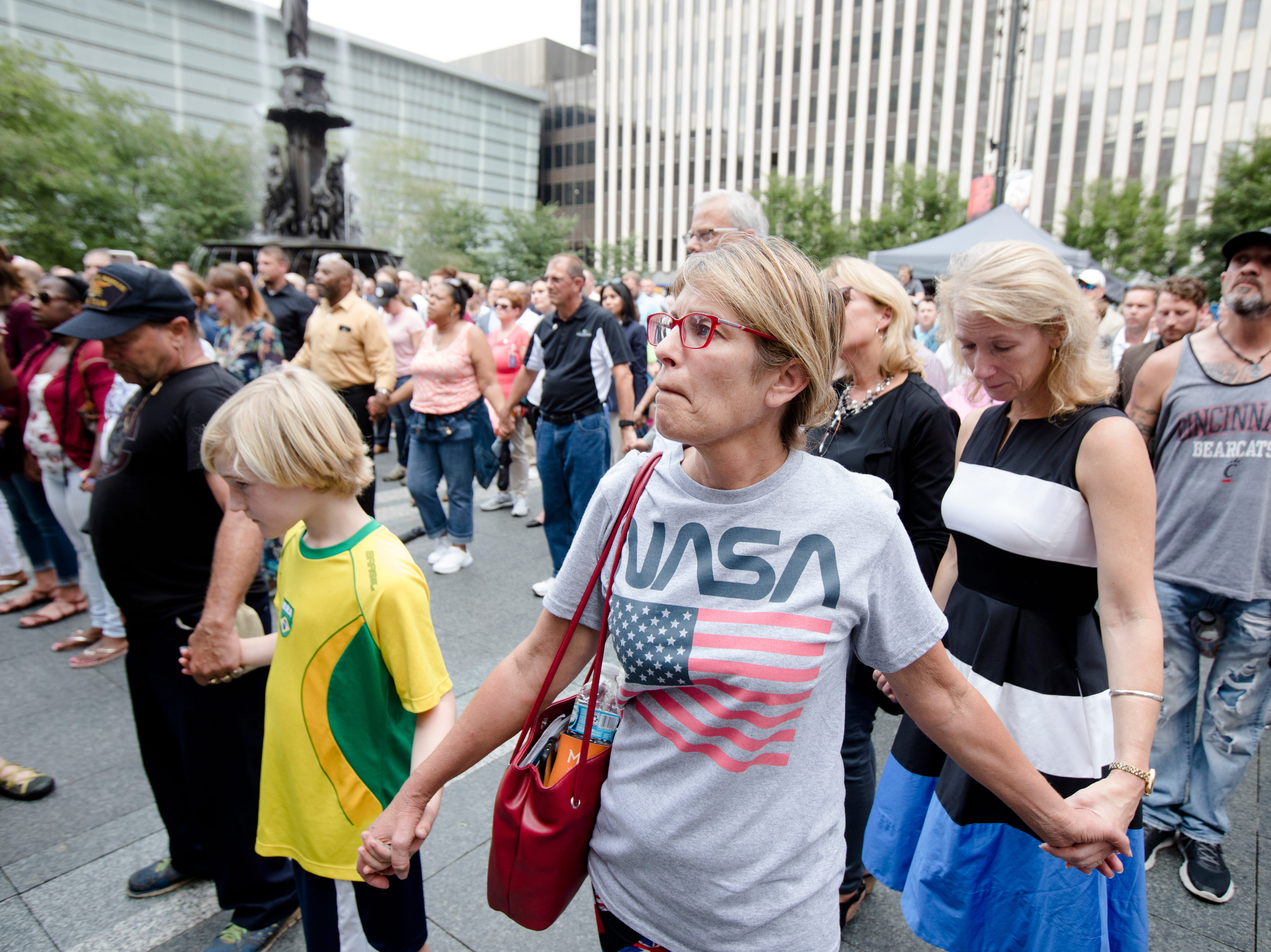 Nancy Pessler, center, holds the hands of others during a vigil on Friday, Sept. 7, 2018, for the victims of a mass shooting in Downtown Cincinnati. Omar Santa Perez killed three people on Thursday.
