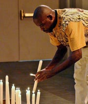 Desmond Brown lights a candle at a Litany in the Aftermath of Gun Violence at Christ Church Cathedral in Downtown Thursday night.