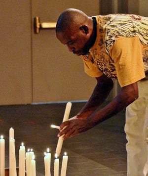 Desmond Brown lights a candle at a Litany in the Aftermath of Gun Violence at Christ Church Cathedral in Downtown after the Fifth Third shooting earlier this month.