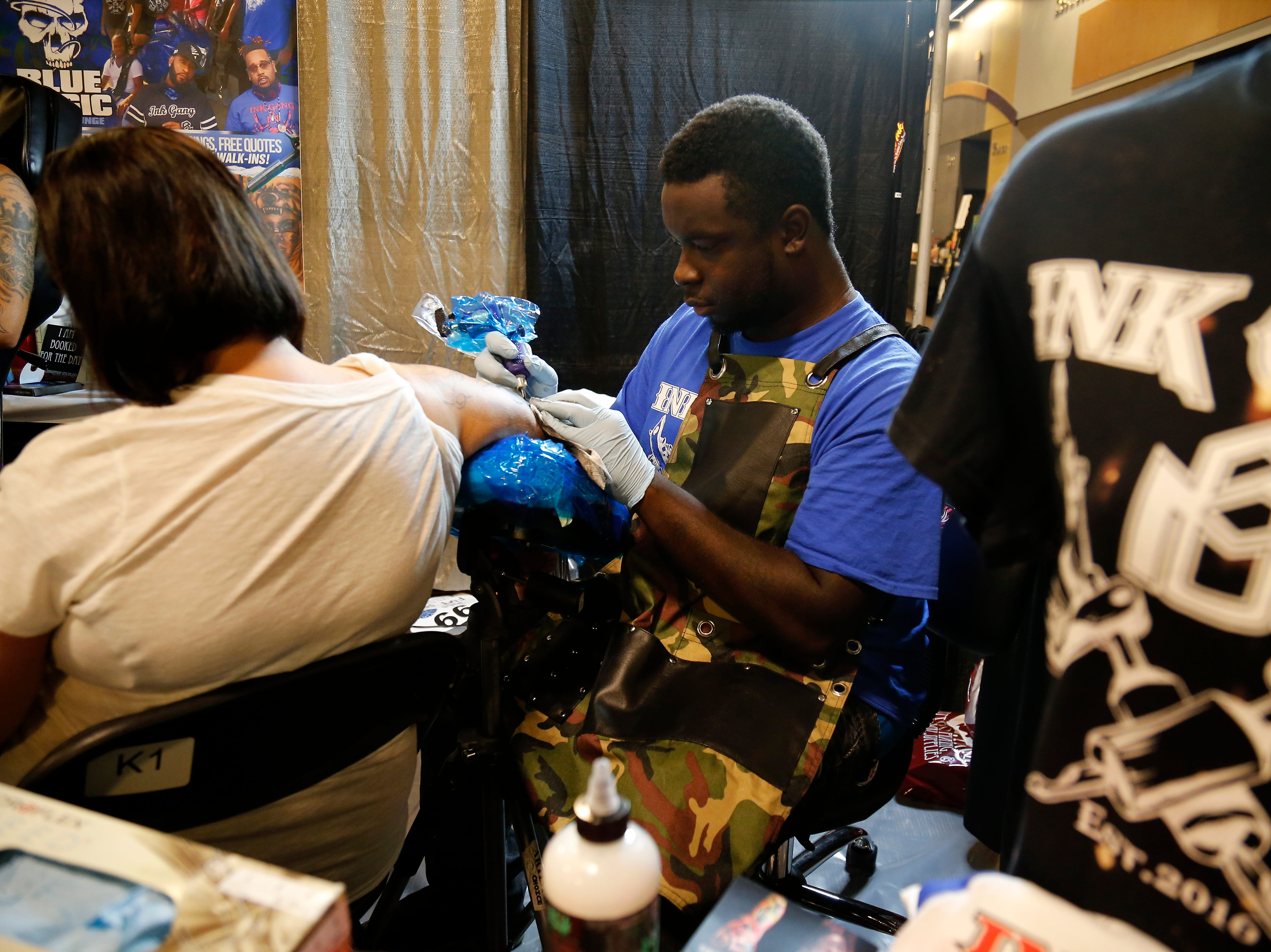 Demetrius Coleman of Blue Magic Tattoo Lounge in Cincinnati tattoos during the Greater Cincinnati Tattoo Arts Convention at the Northern Kentucky Convention Center in Covington, Ky., on Friday, Sept. 7, 2018.