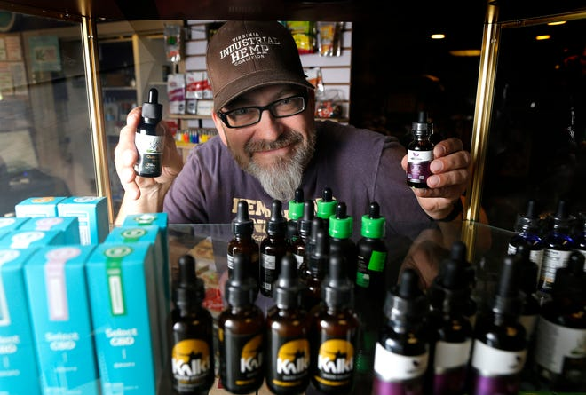 "Hemptations chain owner E.R. Beach poses with a display of CBD oil in the form of drops at the Hemptations ""Hempquarters"" in Sharonville, Ohio, on Friday, Sept. 7, 2018."