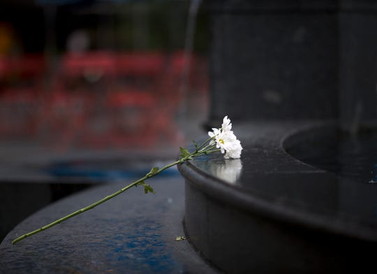 Flowers are laid on The Tyler Davidson fountain on Fountain Square. The square is back open the day after a gunman opened fire leaving four dead, including the shooter, and two injured.