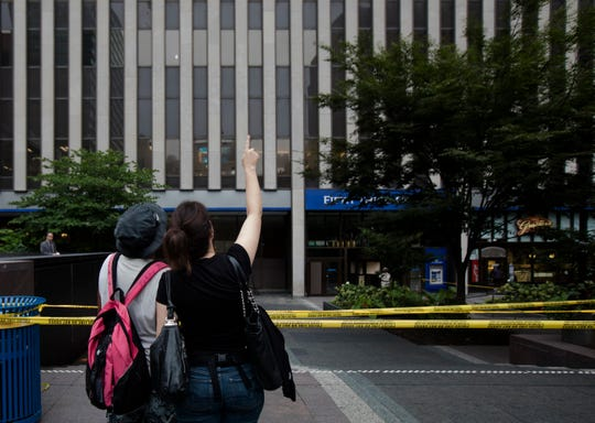 A Fifth Third Bank employee points up at the office floor she was on the day before while speaking to a friend in Fountain Square on Friday, Sept. 7, 2018, in Downtown Cincinnati.  The square is was opened Friday morning after a gunman opened fire leaving four dead inside the Fifth Third Bank building, including the shooter, and two injured.