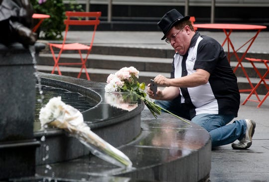 John Rabold takes a picture of flowers on Fountain Square on Friday, Sept. 7, 2018, in Downtown Cincinnati.  The square is was opened Friday morning after a gunman opened fire leaving four dead, including the shooter, and two injured.