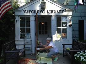 Coalition to Save Watchung Library volunteer Angela Della Ventura looks up from power sanding the door to the Watchung Library, preparing it for repainting.