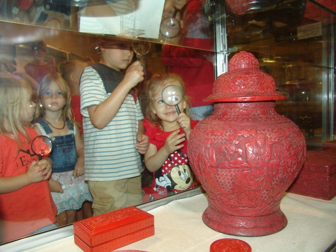 Piper McDonald uses a magnifying glass to look at pieces on display in the Asian Gallery at the Johnson-Humrickhouse Museum.