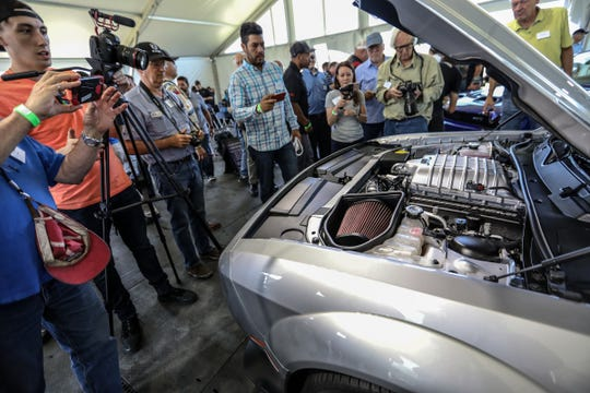 """Journalists crowd around to get a look at the engine of a 2019 Dodge Challenger SRT Hellcat Redeye during the """"What's New"""" event ate Chelsea Proving Grounds in Chelsea on Thursday, June 28, 2018."""