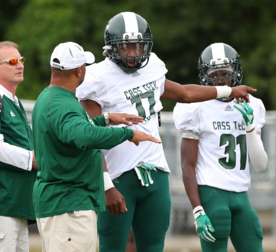 Cass Tech head coach Thomas Wilcher talks with Jalen Graham during action against Henry Ford on Friday, Sept. 7, 2018 at Henry Ford in Detroit.