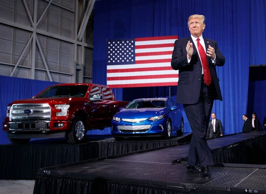 President Donald Trump arrives to speak at the American Center of Mobility, Wednesday, March 15, 2017, in Ypsilanti Township. In the background is a Ford F-150 and a Chevrolet Volt.