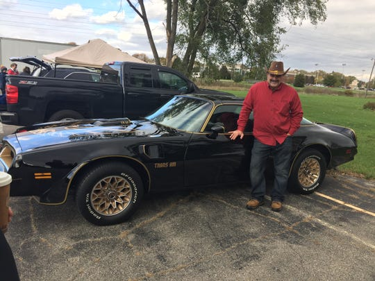 "Mark Piccalo of Warren wears his ""Bandit"" Halloween outfit and stands beside his 1977 Pontiac Trans Am like the one used in the Burt Reynolds movie ""Smokey and the Bandit."""