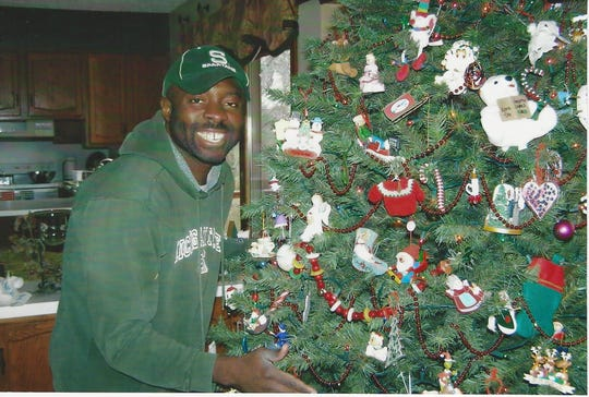 Francis Anwana, 48, an immigrant from Nigeria, stands next to a Christmas tree, in Michigan. He's lived in the U.S. since he was 14, but now faces deportation.