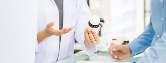 Female Pharmacist Holding Medicine Bottle Giving Advice To Customer In Chemist Shop Or Pharmacy