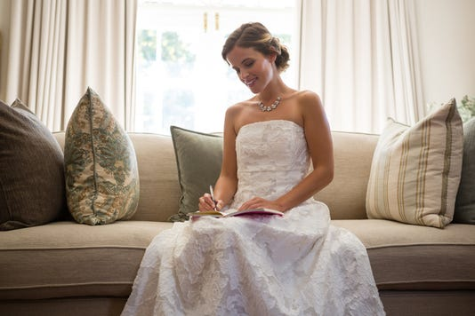 Beautiful Bride Writing In Diary While Sitting On Sofa At Home