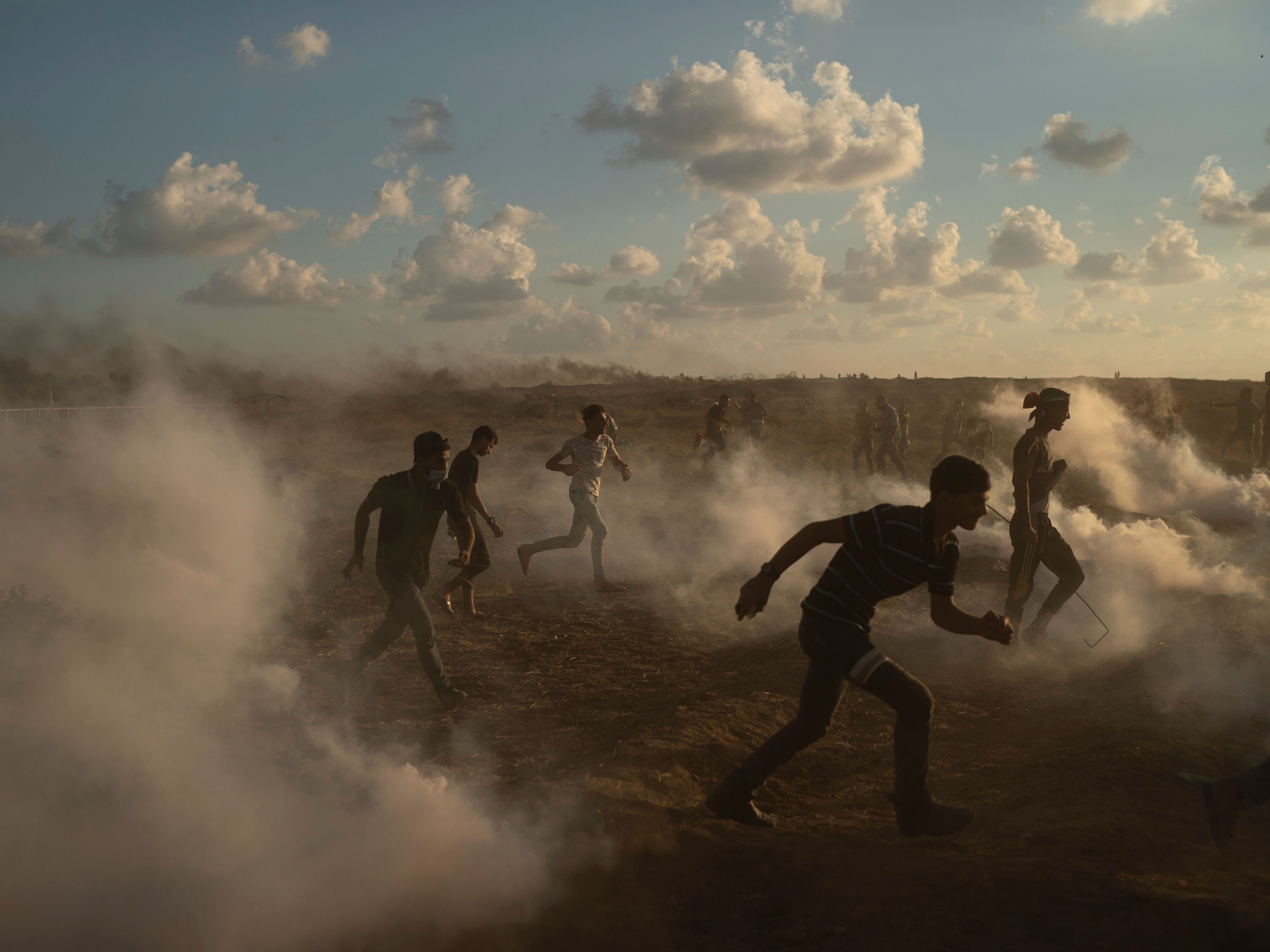 Palestinian protesters run from tear gas fired by Israeli troops during a protest at Gaza Strip's border with Israel, east of Gaza City, Friday, Sept. 7, 2018. A teenager was killed and dozens of other Palestinians injured by Israeli fire at a border protest, Gaza officials said.