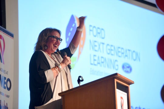 Cheryl Carrier, executive director, Ford Next Generation Learning, raise her arm in celebration during a designation ceremony held at Powell Middle School on Friday, September 7, 2018 as she announced The Academies at Romeo.