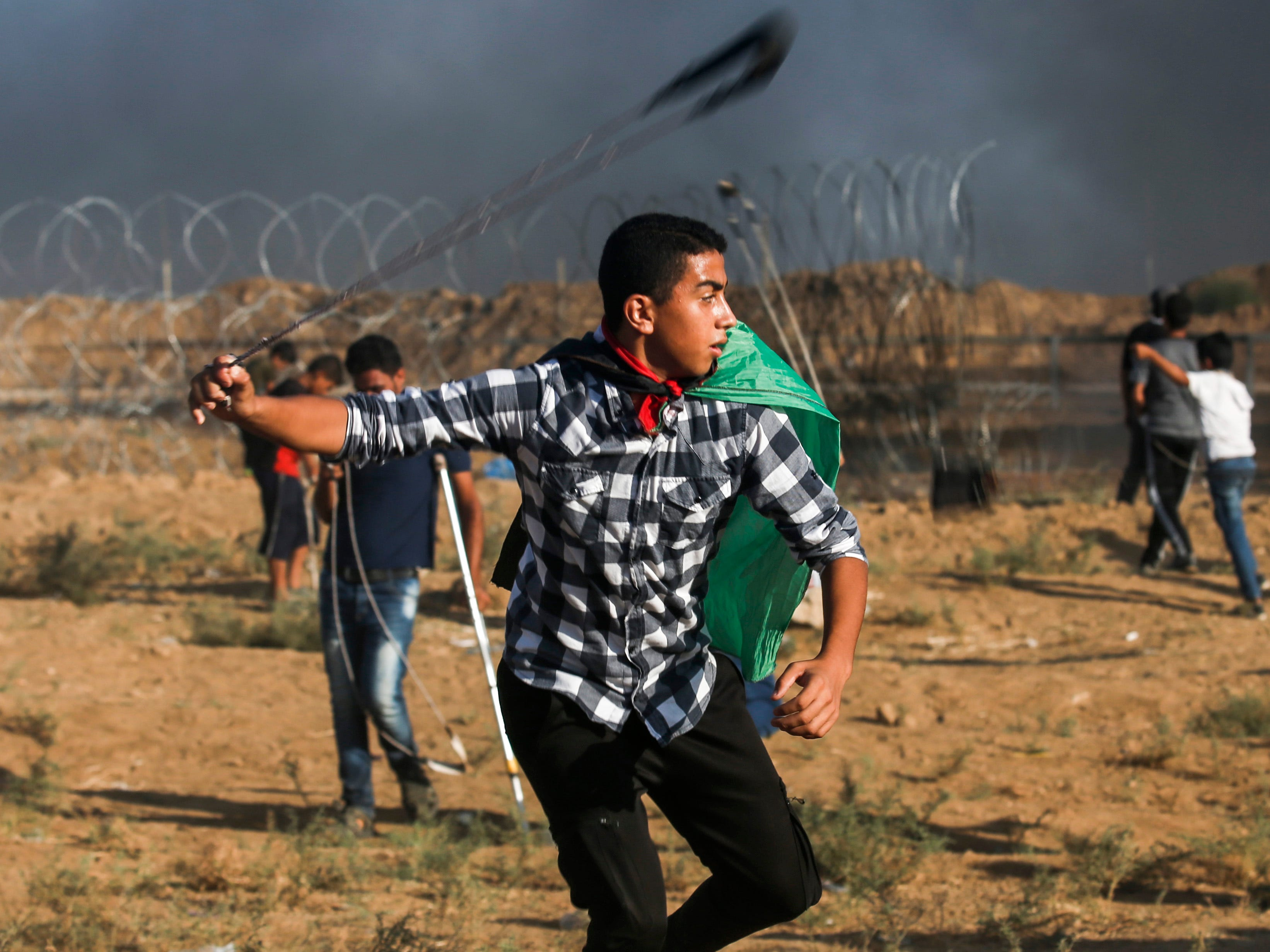 A protester wearing a Palestinian flag uses a slingshot to hurl stones at Israeli forces during clashes following a demonstration at the Israel-Gaza border, east of Gaza City in the central Gaza Strip on Sept. 7, 2018.