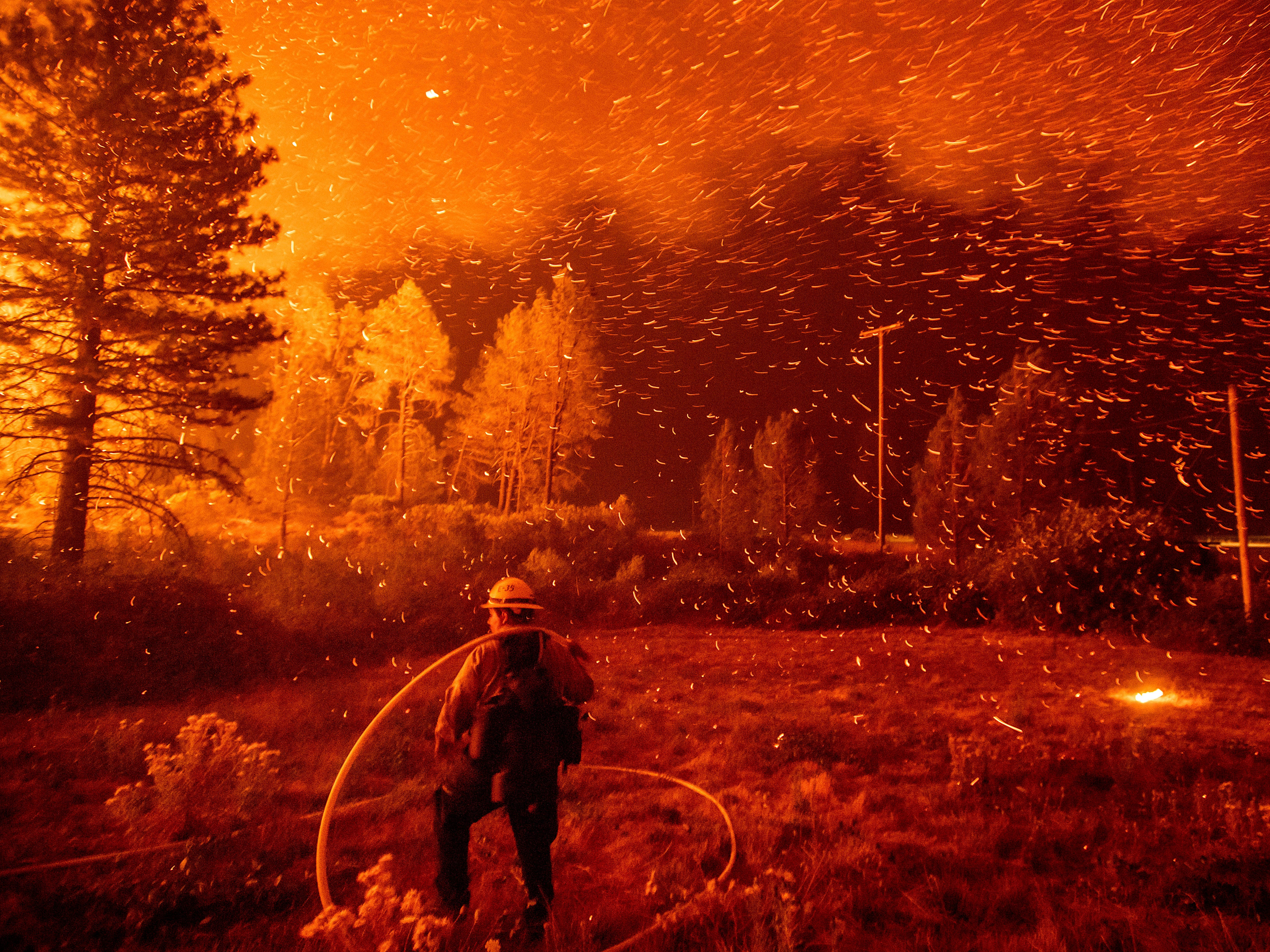 Embers fly above a firefighter as he works to control a backfire as the Delta Fire burns in the Shasta-Trinity National Forest, Calif., on Thursday, Sept. 6, 2018. The blaze had tripled in size overnight.