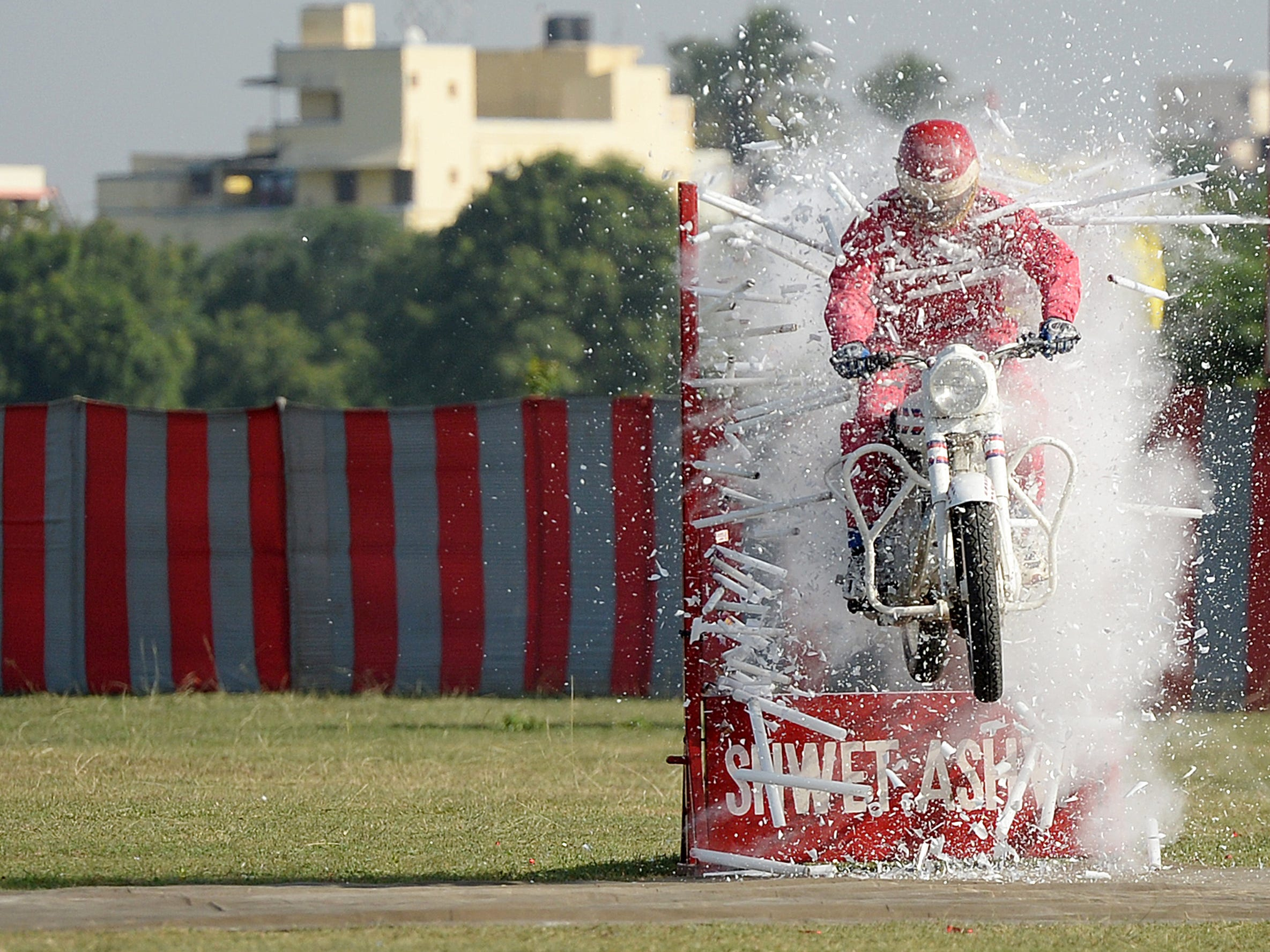An Indian army soldier, a member of a motorcycle display team, performs a stunt at an officer training academy in Chennai on Friday, Sept. 7, 2018.