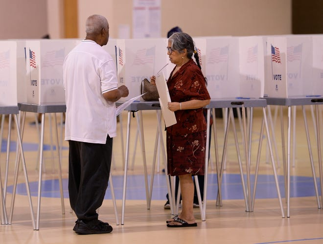 l-r, Melvin Taylor, 83, and his wife Marcia Taylor of Pontiac talk after casting their votes this morning at New Bethel Missionary church.***Voters and campaign workers at New Bethel Missionary Baptist church. August 7, 2018, Pontiac, MI.