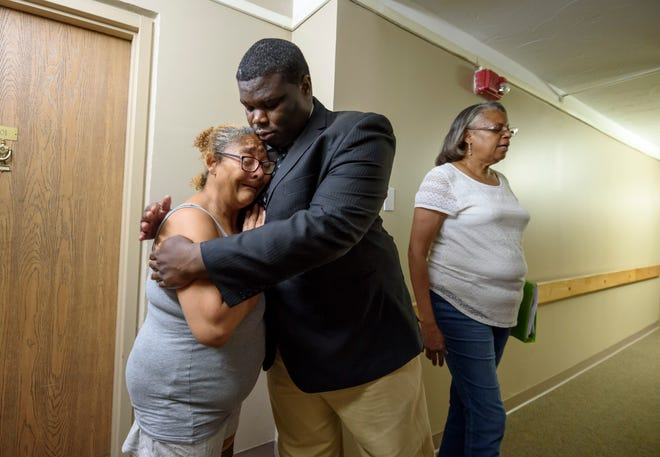 Tenant Katherine Tiller gets a hug from Detroit Police Commissioner Willie Burton as she recounts a violent incident she experienced in the elevator inside the Parkview Place apartments in Detroit. At right is Katherine Richardson, president of the tenant council for the building.