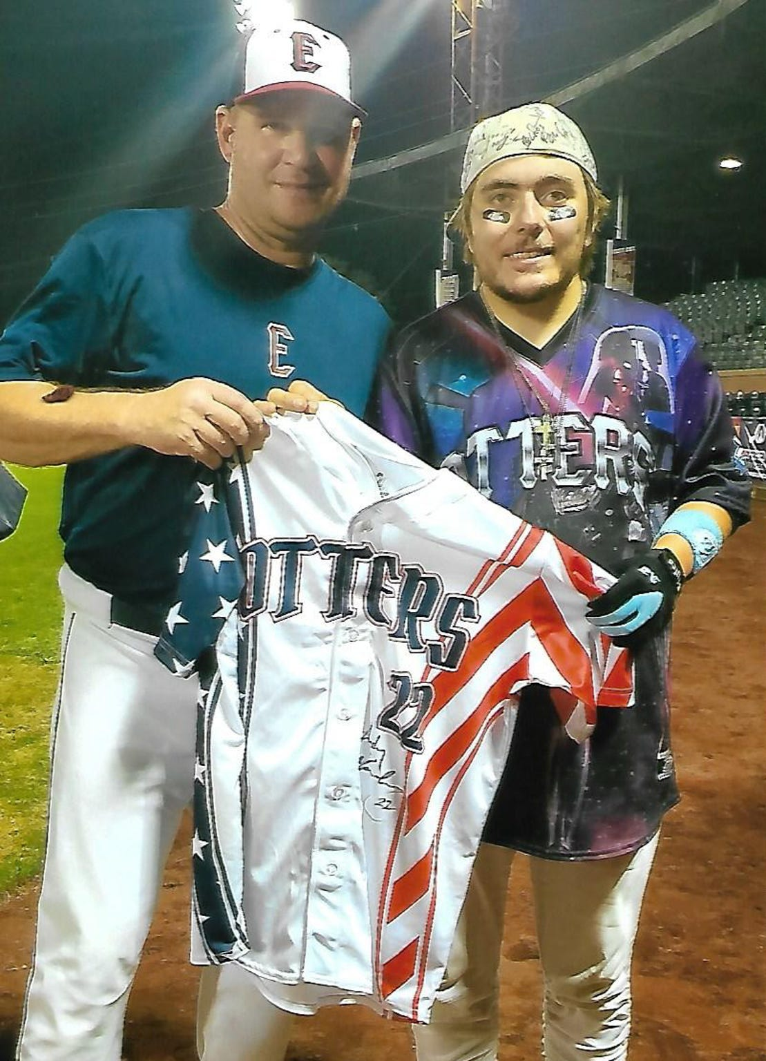 Evansville Otters' manager Andy McCauley (left) presents his game-worn jersey to superfan Nick Drake from Military Appreciation Night on Aug. 25.