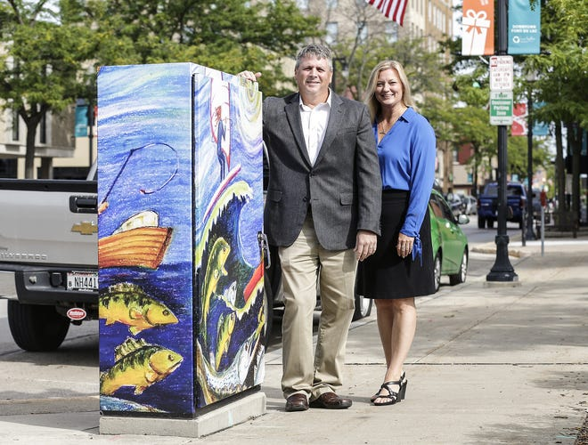 Joe Braun of the Fond du Lac Area Foundation and Amy Hansen of the Downtown Fond du Lac Partnership, Inc. stand next to a wrapped utility box Friday, Sept. 7, 2018, in downtown Fond du Lac.