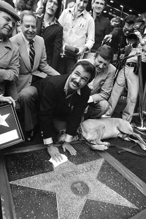 """In this March 15, 1978 file photo, actor Burt Reynolds polishes star that was unveiled in the Hollywood Walk of Fame in Los Angeles. Reynolds, who starred in films including """"Deliverance,"""" """"Boogie Nights,"""" and the """"Smokey and the Bandit"""" films, died at age 82, according to his agent."""