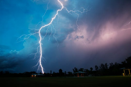 A bolt of lightning strikes in Fort Myers near Lakes Park on Thursday evening as a thunderstorm rolls through the area. This summer there has been more than 2 feet less rain than the same period last year.