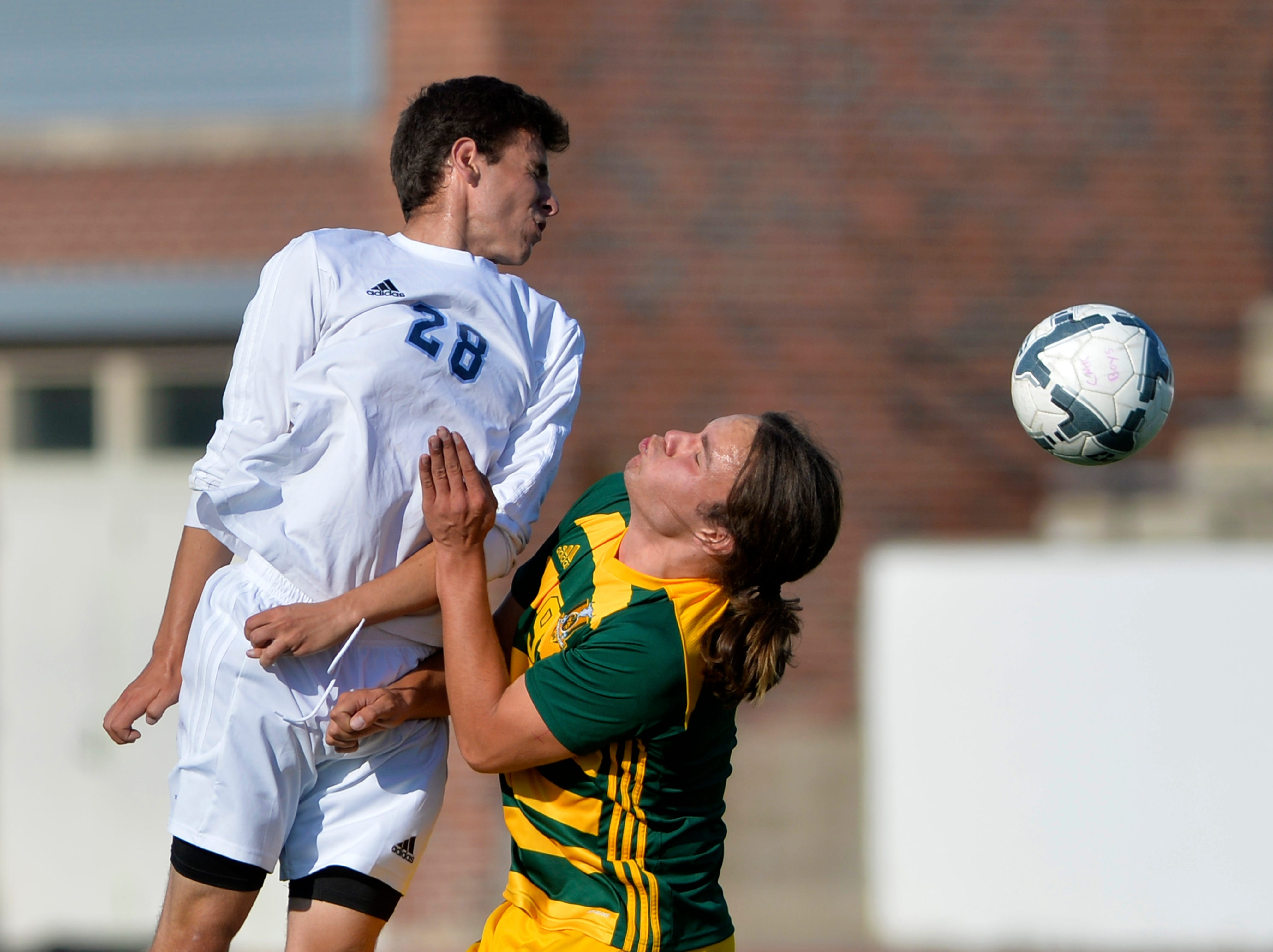 Great Falls High's Brian Gemberling wins a header over CMR's Seamus Jennings during the crosstown soccer match at Memorial Stadium, Thursday, Sept. 6, 2018.
