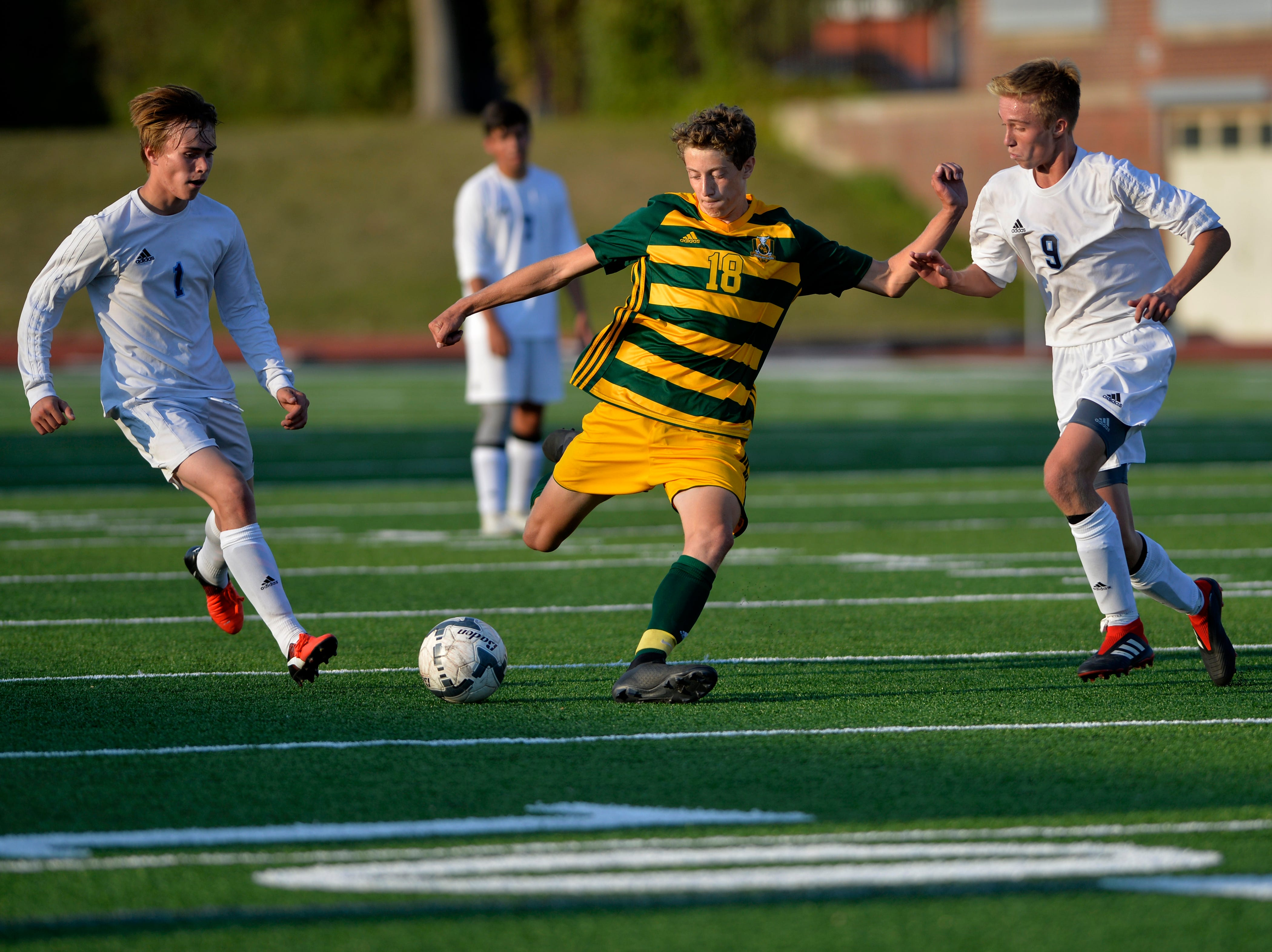 CMR's Statton Bohl, 18, makes a pass as Great Falls High's Trevin Smith, 1, and Gavin Groshelle, 9,  defend during the crosstown soccer match at Memorial Stadium, Thursday, Sept. 6, 2018.