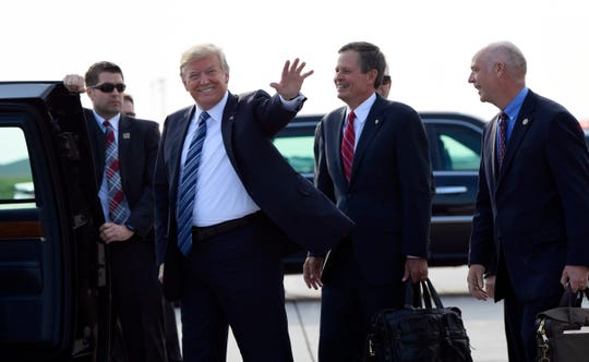President Donald Trump waves as he walks off of Air Force One at Billings Logan International Airport in Billings, Mont., Thursday, Sept. 6, 2018, with Sen. Steve Daines, R-Mont., second from right, and Rep Greg Gianforte, R-Mont. Trump is in Montana for a rally. (AP Photo/Susan Walsh)