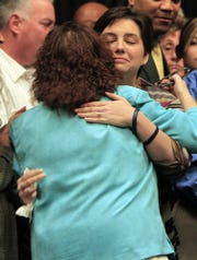 Mary Moriarty-Adams hugs Jamie Bradway, widow of fallen IMPD Officer Rod Bradway, after a resolution to honor his life on Nov. 11, 2013.