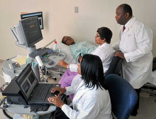 The Jackson Heart Study has been renewed. Since 1998, the NIH-funded project has enabled researchers at UMMC, Jackson State University and Tougaloo College to study cardiovascular health and disease in African Americans. The study includes physical exams, like the one shown here from 2012 where Dr. Ervin Fox, professor of medicine, monitors as Shari Cook, foreground, and Audrey Samuels, center, take readings from a participant.